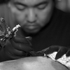 The Golden Needle Tattoo Studio, Phuket Town, Thailand. Tattoo artist Mee goes to work